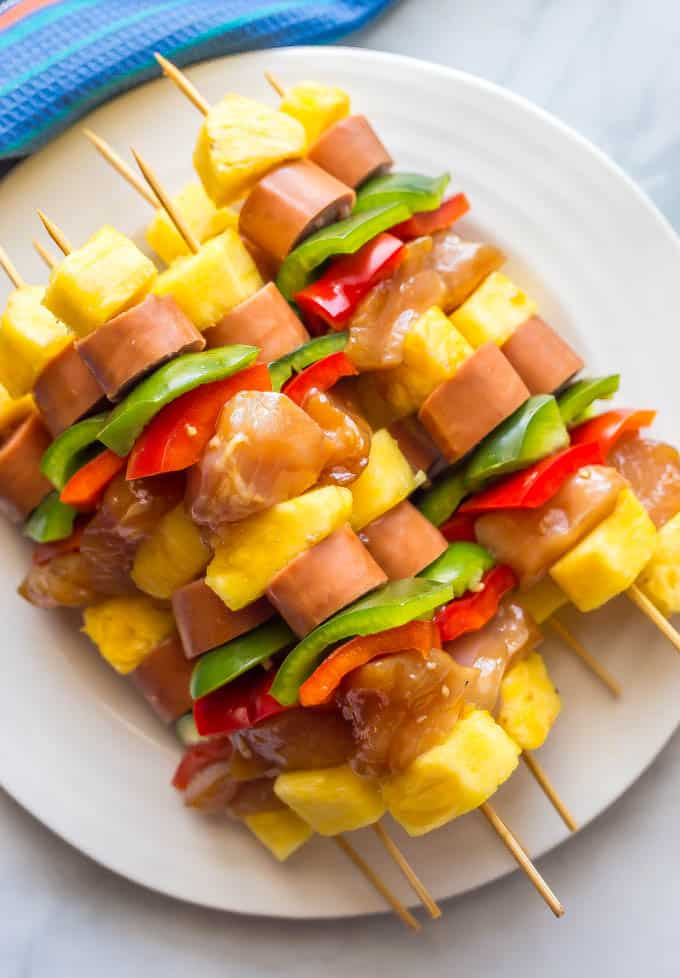 Teriyaki chicken kabobs on a white plate threaded onto skewers before being grilled