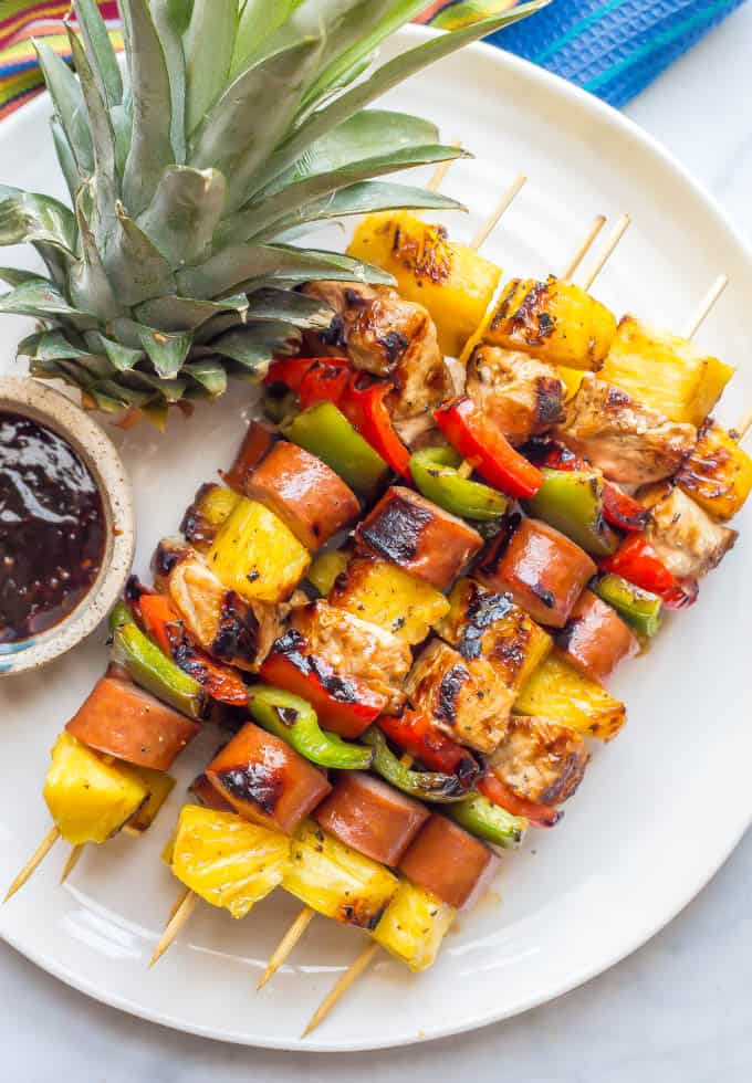Grilled teriyaki chicken kabobs on a white plate with a small bowl of teriyaki sauce nearby