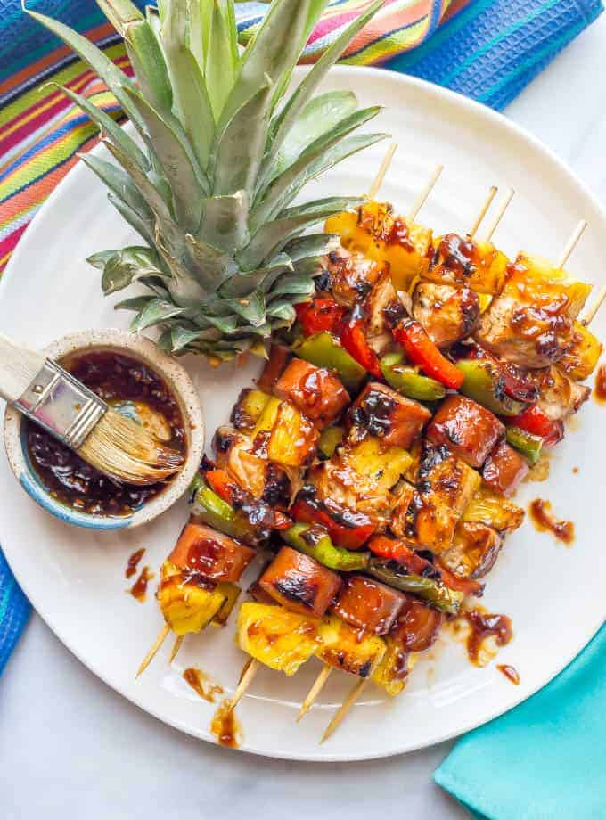 Grilled teriyaki chicken kabobs on a white plate with extra teriyaki sauce on top