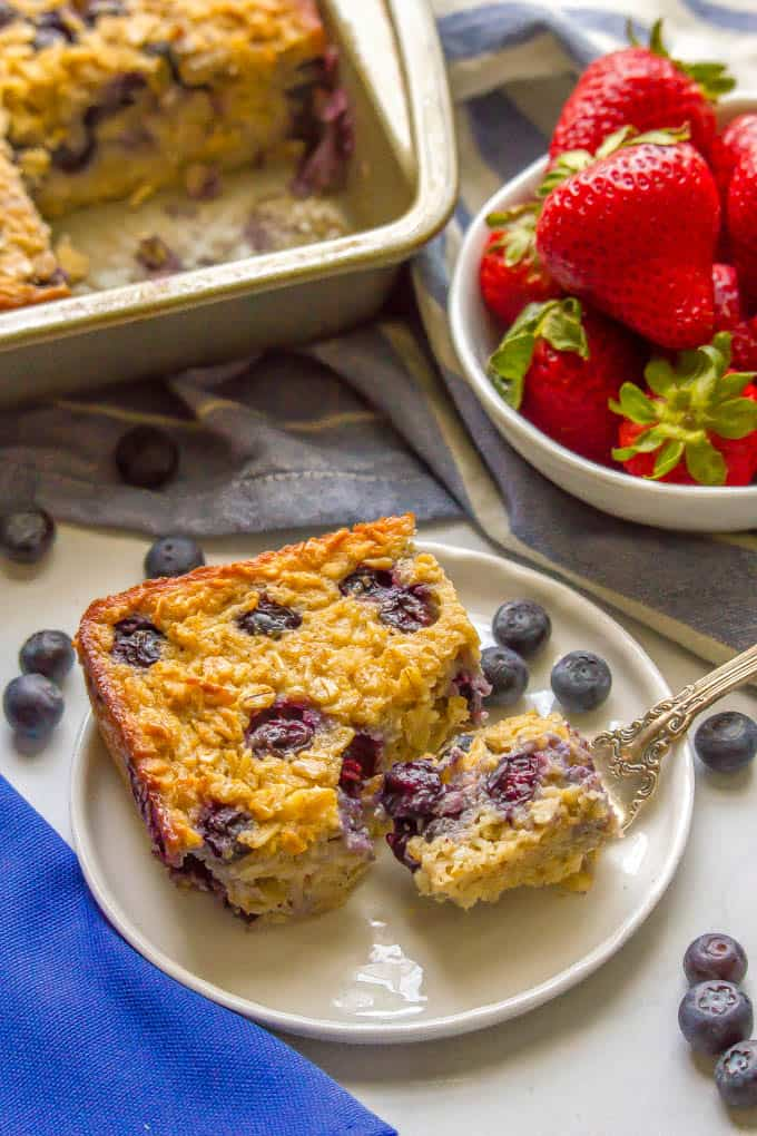 A piece of blueberry baked oatmeal on a white plate with a bite resting on a fork and fresh berries nearby