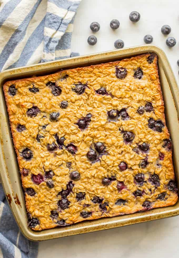 Blueberry baked oatmeal in a pan after being baked with fresh blueberries scattered nearby