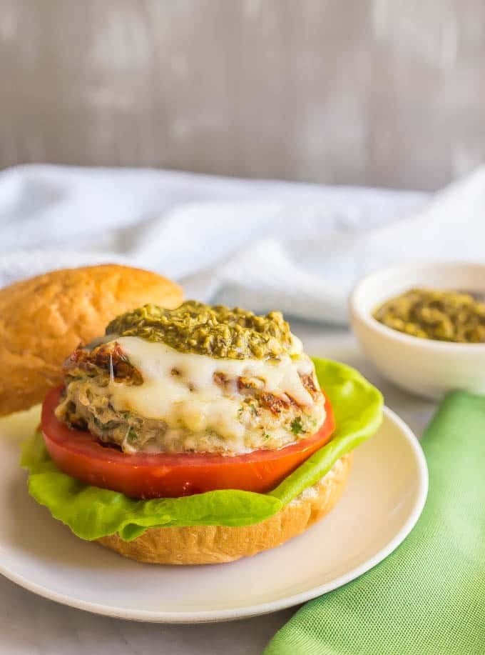 Chicken spinach burger topped with mozzarella cheese and pesto on a bun with lettuce and tomato