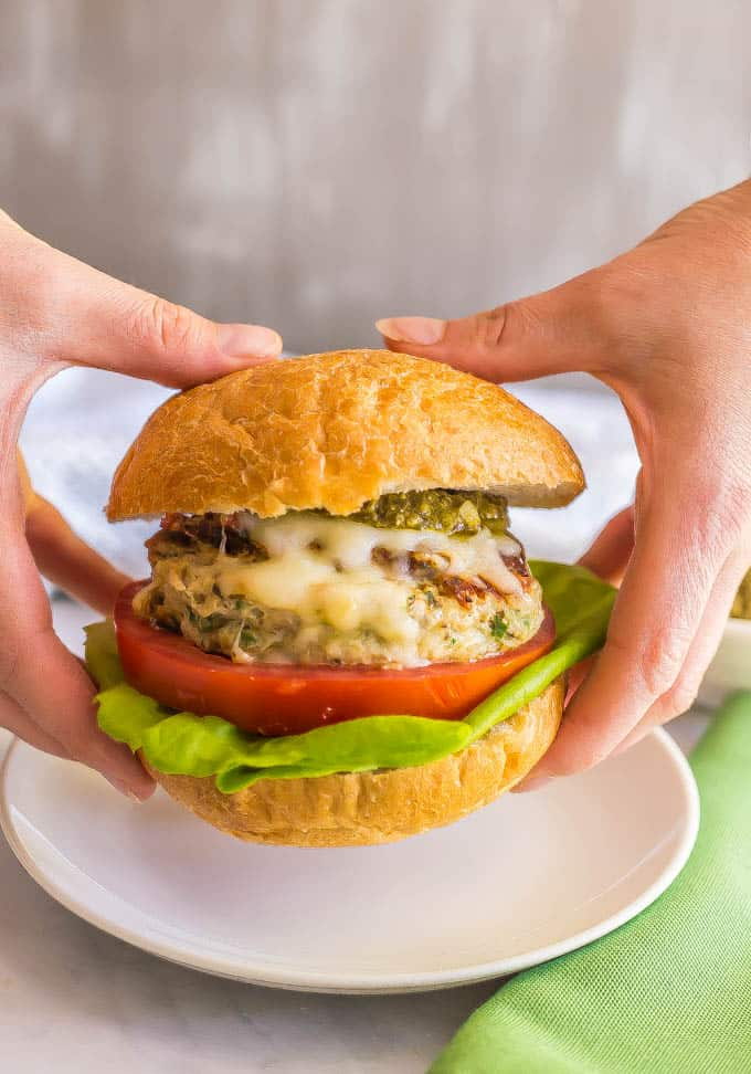 Chicken spinach burgers have just 5 ingredients and are full of cheesy shredded mozzarella, chopped fresh spinach and rich flavor from the touch of pesto. Top with extra mozzarella and pesto and serve on buns or in a lettuce wrap for a delicious, healthy burger! #chickenburger #groundchicken #healthyburger | www.familyfoodonthetable.com