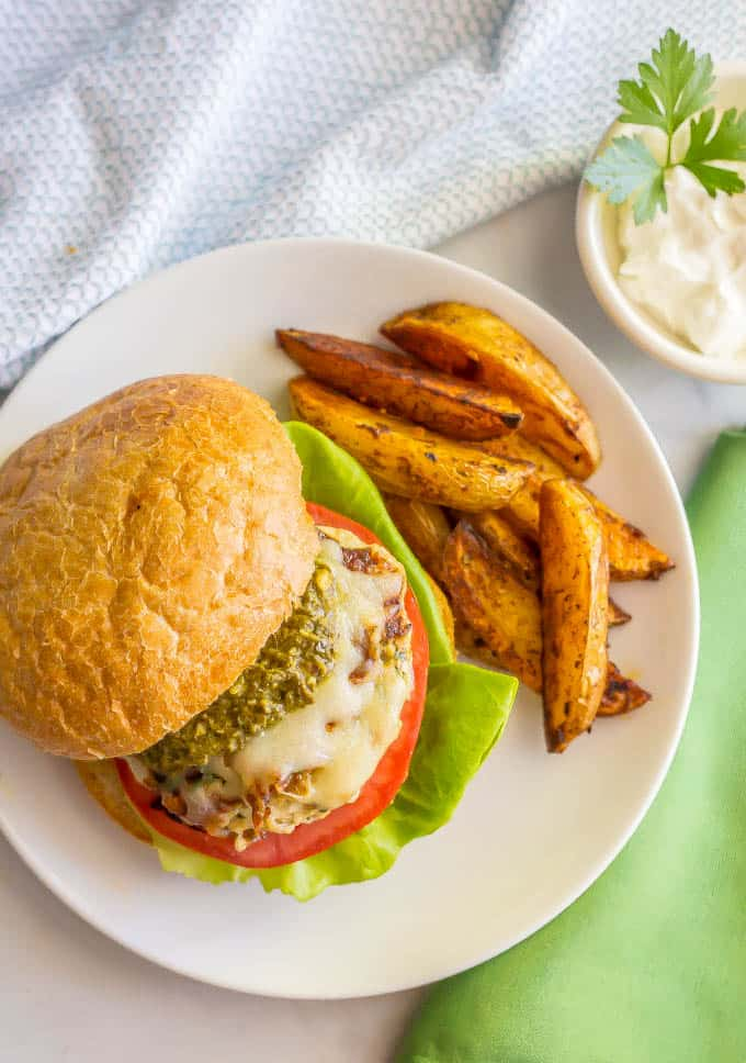 Chicken spinach burger with mozzarella and pesto on a plate with roasted potatoes