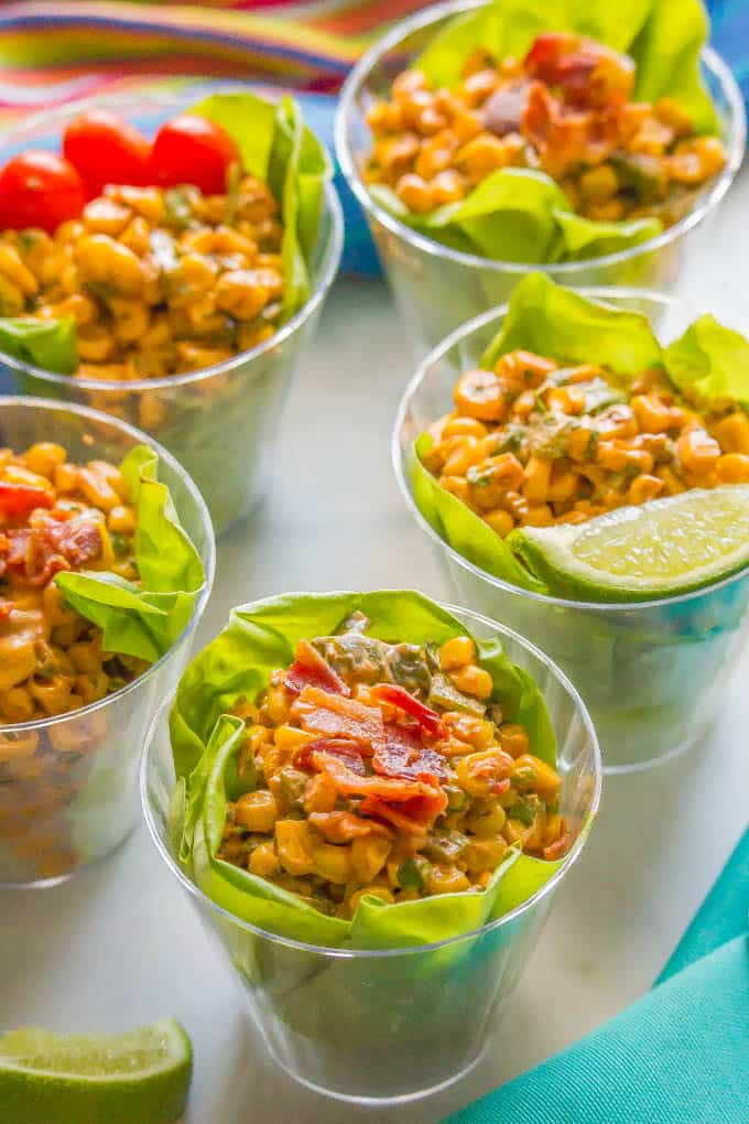 Summer corn salad cups served individually with bacon, tomatoes and lime toppings