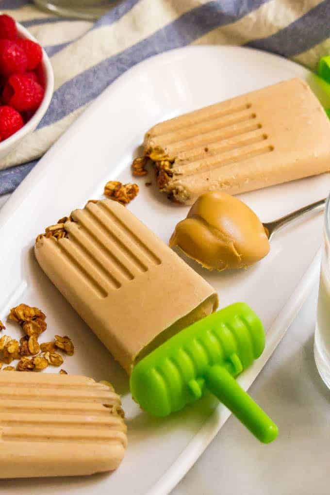 Healthy breakfast popsicles are naturally sweetened and made with just 5 ingredients. The creamy peanut butter and banana flavor is addictive and the crushed cereal or granola brings a fun texture! #popsicles #peanutbutter #summertreat #healthykids #summerfun