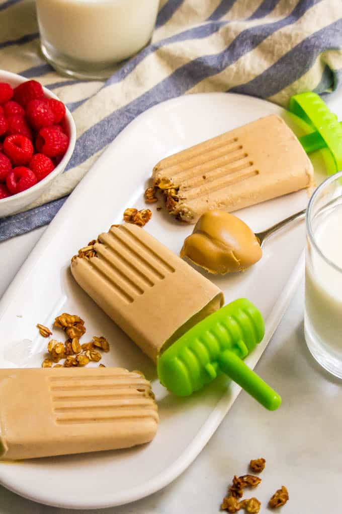 Healthy breakfast popsicles on a plate with granola and a dollop of peanut butter