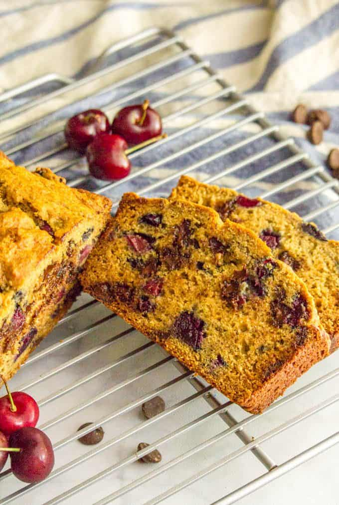 Slices of whole wheat cherry chocolate chip bread on a cooling rack