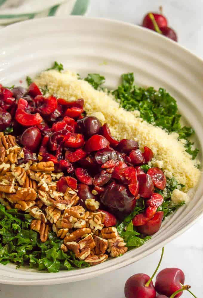 Layered ingredients for massaged kale salad with cherries in a large white bowl