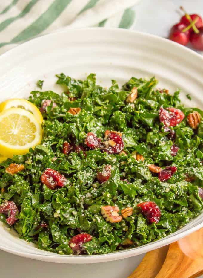 Mixed massaged kale salad with cherries, pecans and Parmesan cheese in a large white bowl with lemon slices on the side