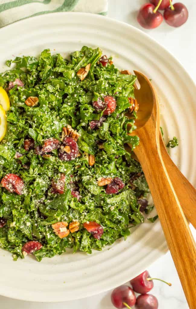 Massaged kale salad with cherries recipe in a large white bowl with wooden serving spoons tucked in