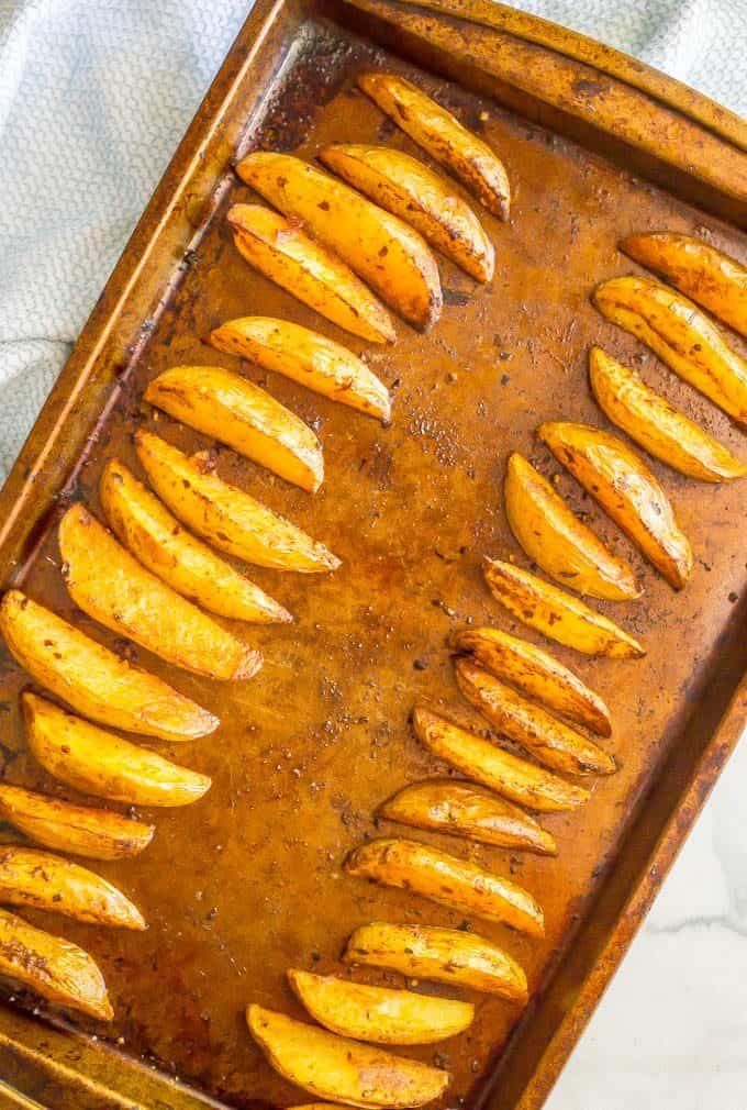 Easy spicy oven roasted potato wedges on a sheet pan after being baked