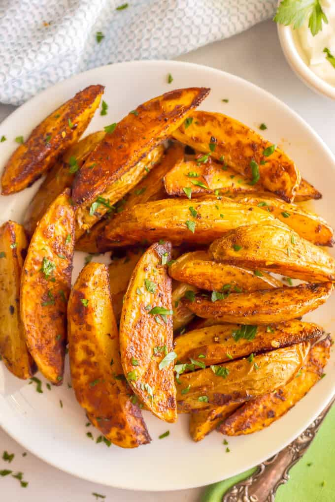 Easy spicy roasted potatoes require just a few pantry ingredients to create a truly delicious side dish with a bit of a kick! These potato wedges are crispy and crunchy on the outside with a tender, fluffy center. #roastedpotatoes #potatoes #spicyfood