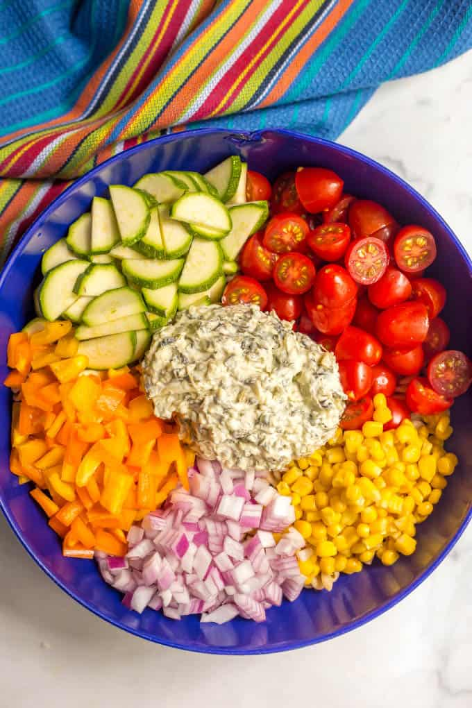 Ingredients layered in a large blue bowl for summer veggie pasta salad with a creamy dressing