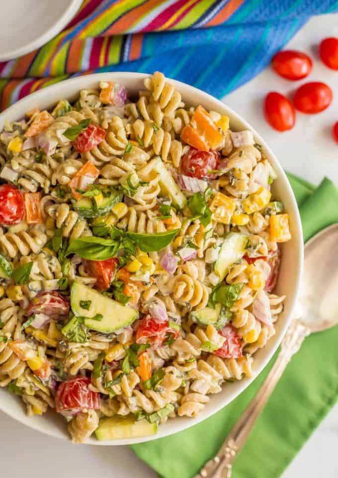 A large white bowl with a pasta salad with tons of fresh veggies and a light creamy dressing mixed in