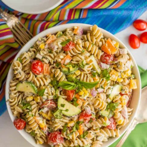 Summer veggie pasta salad in a large white bowl with colorful napkins nearby and a serving spoon