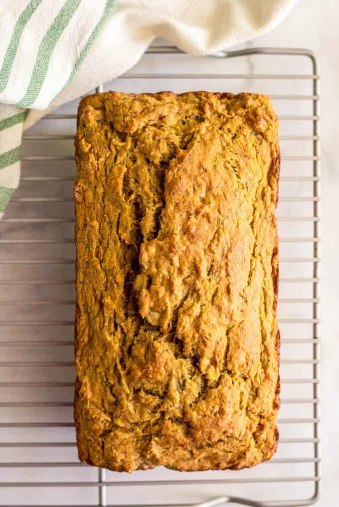 A loaf of whole wheat zucchini banana bread cooling on a wire rack