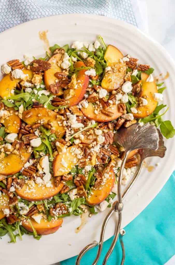 Peach arugula salad with pecans and goat cheese in a large white serving dish with salad tongs