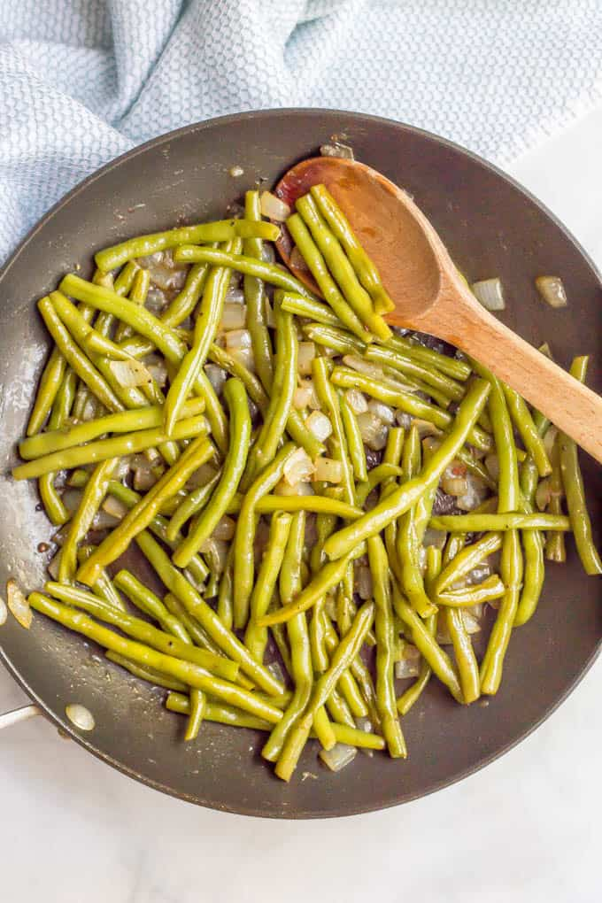 Green beans sautéed with onions in a skillet