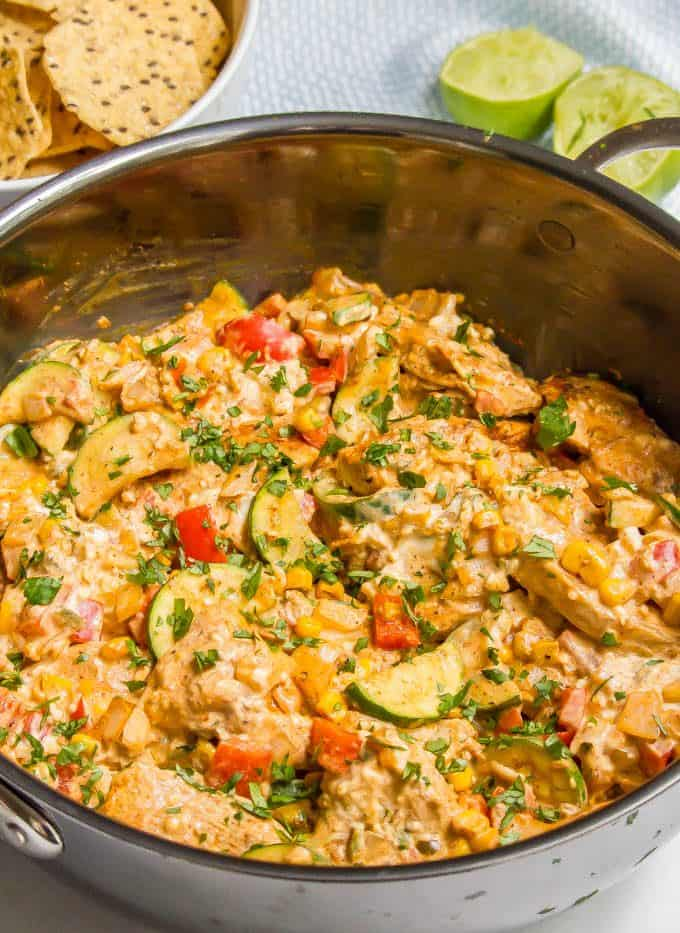 Queso chicken skillet with vegetables in a large skillet with cilantro sprinkled on top