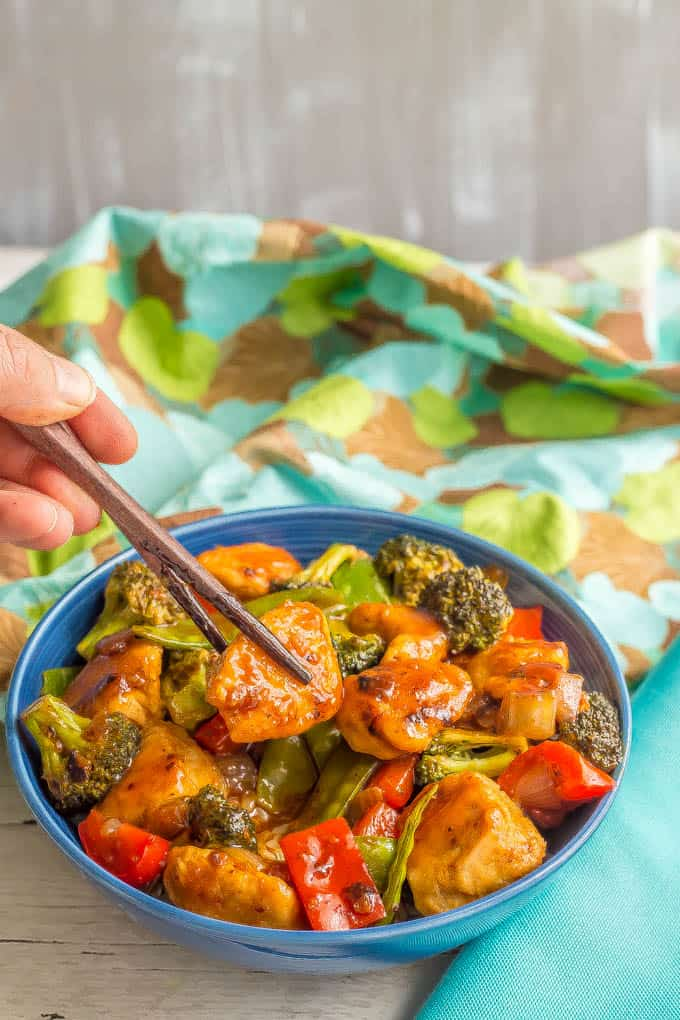 Healthy, easy sweet and sour chicken with vegetables served in a blue bowl with a bite being lifted out