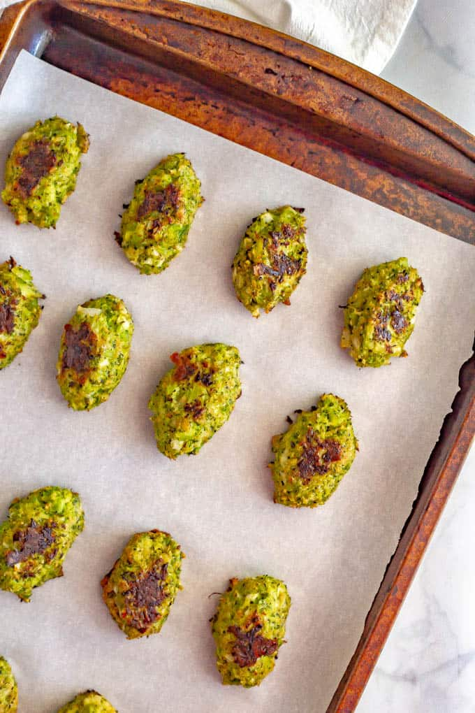 Baked broccoli tots on a baking sheet with parchment paper