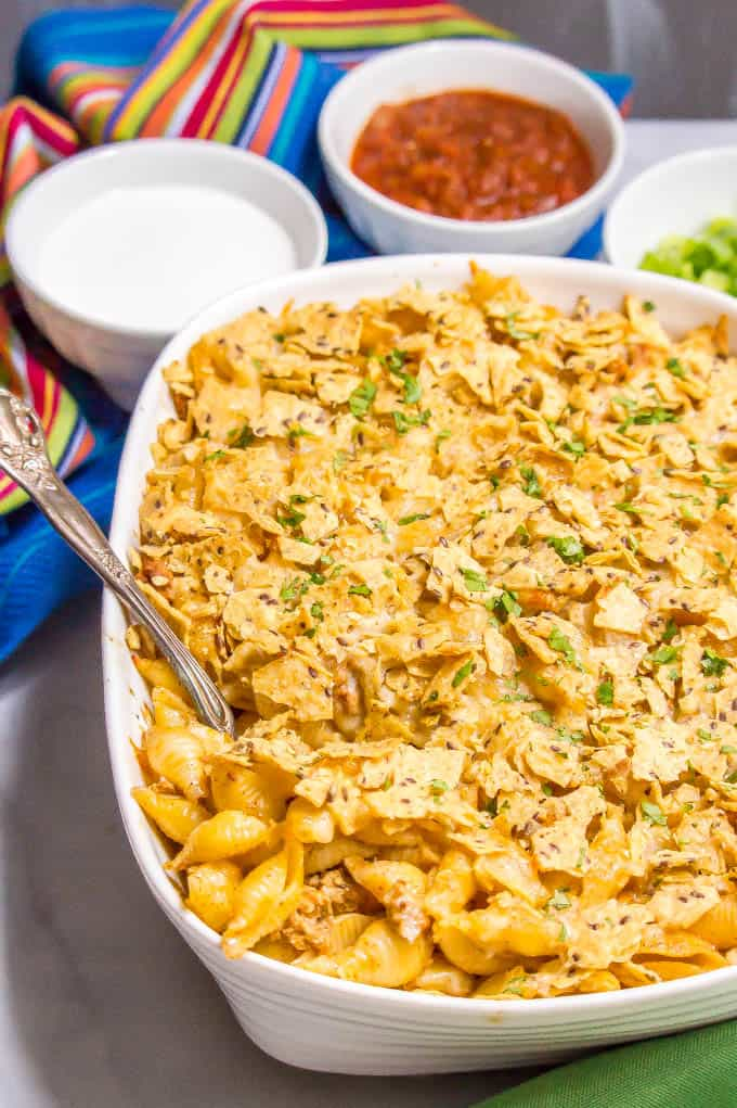 Baked taco mac and cheese casserole is an easy, family-friendly dinner with a creamy sauce and big taco flavor. Add your favorite toppings and dig in! #macandcheese #macaroni #pastadinner #tacos #tacodinner