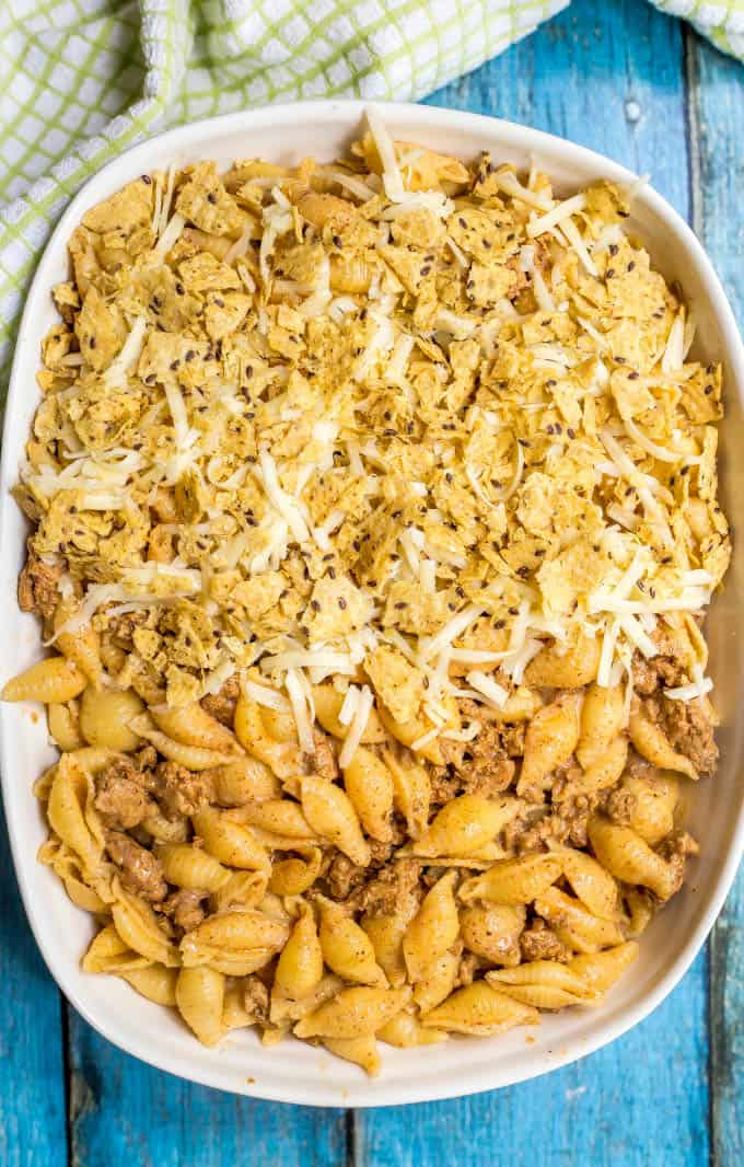 Baked taco mac and cheese casserole being assembled with a tortilla chip and cheese topping
