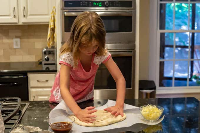 Young girl helping roll out pizza dough