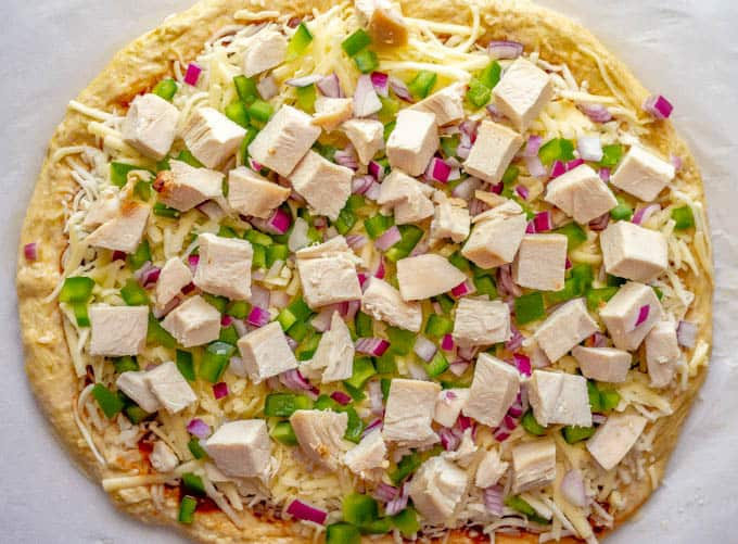 Easy BBQ chicken pizza with peppers and onions before being baked