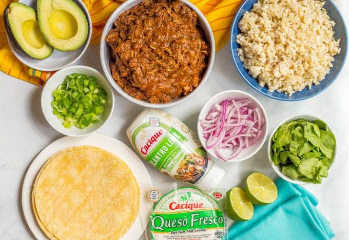 Ingredients for easy crock pot mole chicken laid out in different bowls on a white marble countertop