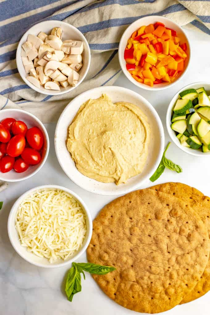 Ingredients for hummus pita pizza with veggies in separate bowls laid out on counter