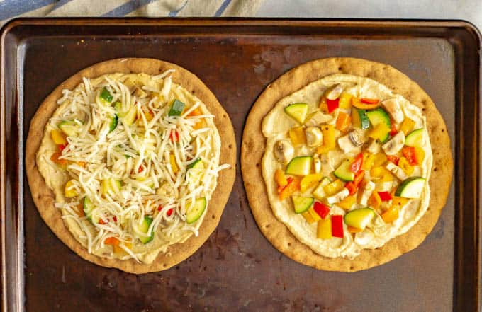 Hummus pita pizzas with veggies and cheese on a baking tray before being baked