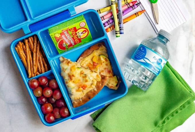 Blue lunchbox with hummus pita pizza with veggies, grapes, pretzels, raisins and a water bottle nearby