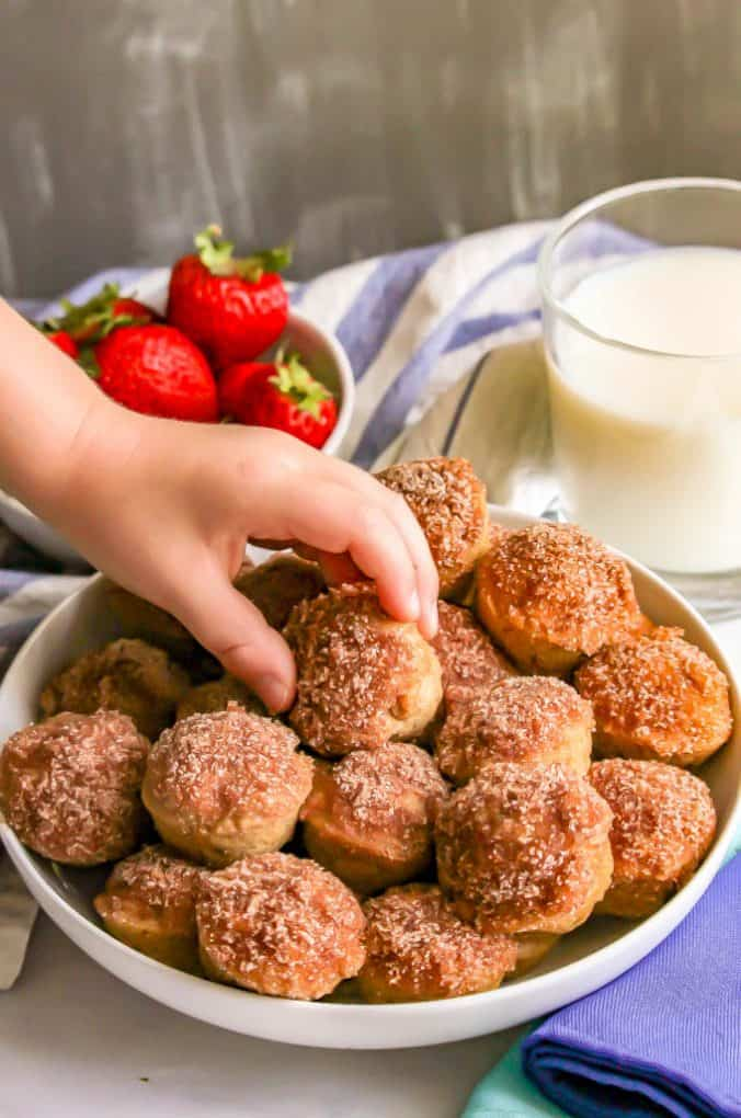 A small hand lifting a baked apple cinnamon donut hole from a bowl