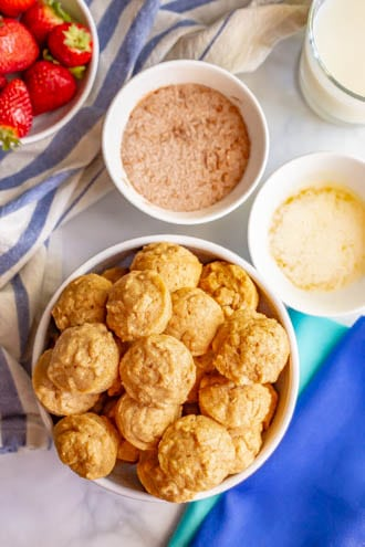 Baked apple cinnamon donut holes piled up in a large bowl and bowls for dunking in a butter and cinnamon sugar coating