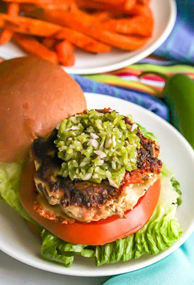 Fresh jalapeno relish piled on top of a loaded burger on a white plate