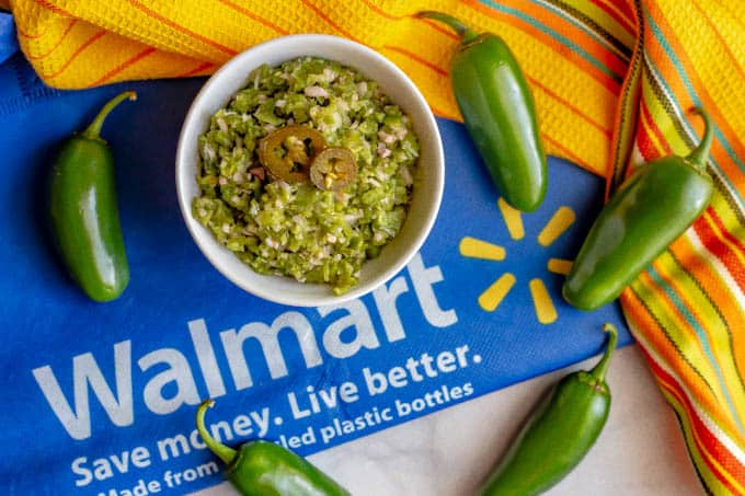 A bowl of easy fresh jalapeño relish with jalapenos scattered around on top of a Walmart bag