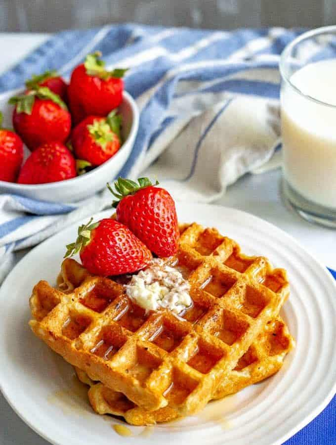 Easy whole wheat waffles are perfectly fluffy on the inside and crispy on the outside. These waffles are naturally sweetened and the extras freeze great! #waffles #breakfast #brunch