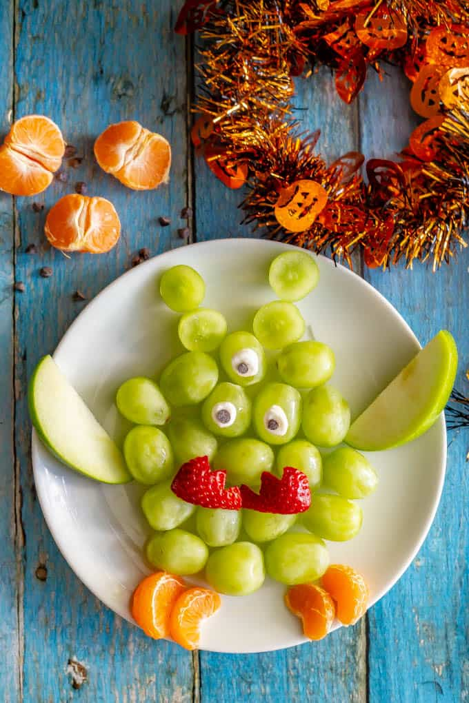 Easy green monster fruit snack on a white plate with oranges, and Halloween decor nearby