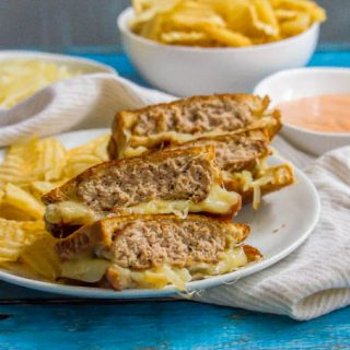 Ground turkey patty melt sandwich sliced and stacked on a white plate with chips on the side