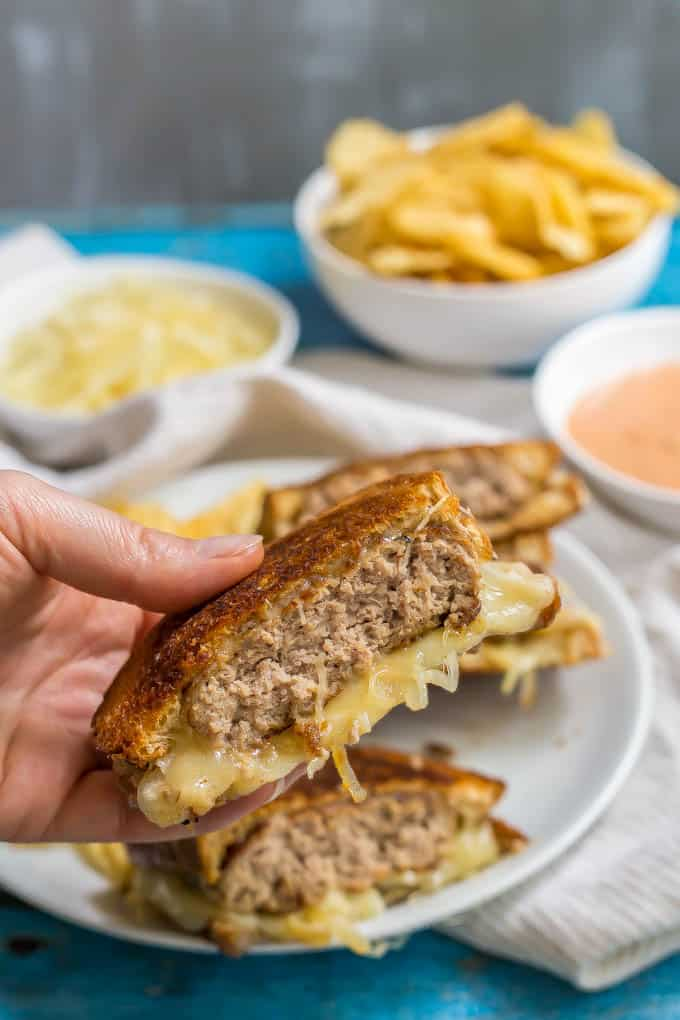 Ground turkey patty melt sandwich being held up with melty cheese