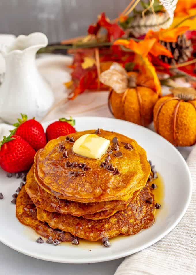 Whole wheat pumpkin pancakes are light, fluffy and full of warm spices and pumpkin flavor. They are naturally sweetened (and can be made vegan) and are perfect for a delicious fall breakfast! #pumpkin #pancakes #breakfast #vegan