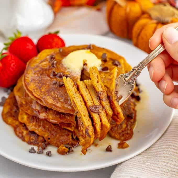 A forkful of a stack of whole wheat pumpkin pancakes about to be eaten