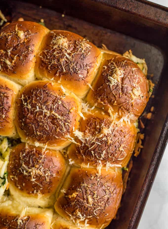 Baked pesto chicken sliders with golden brown tops in a baking pan
