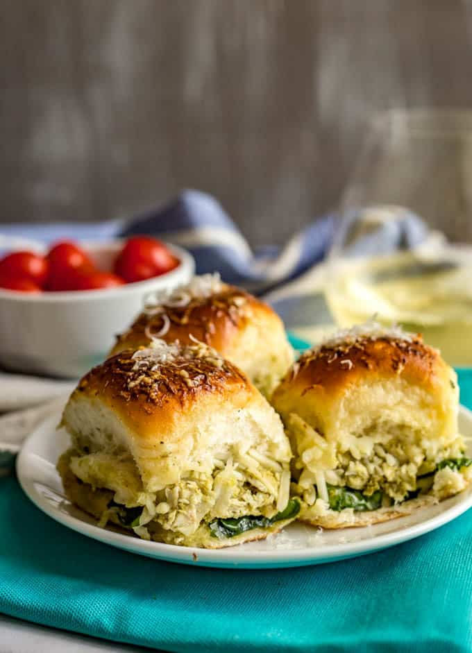 Baked pesto chicken sliders served on a white plate with a turquoise napkin underneath