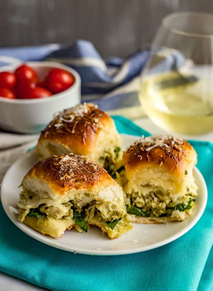 Baked pesto chicken sliders on a plate with a bite taken out of one