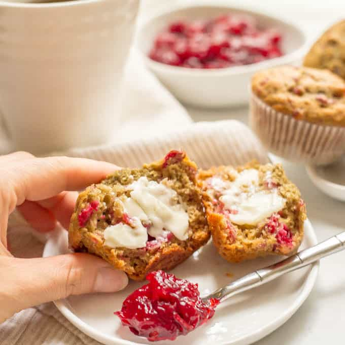 Whole wheat cranberry sauce muffin served on a plate with butter on top and being picked up