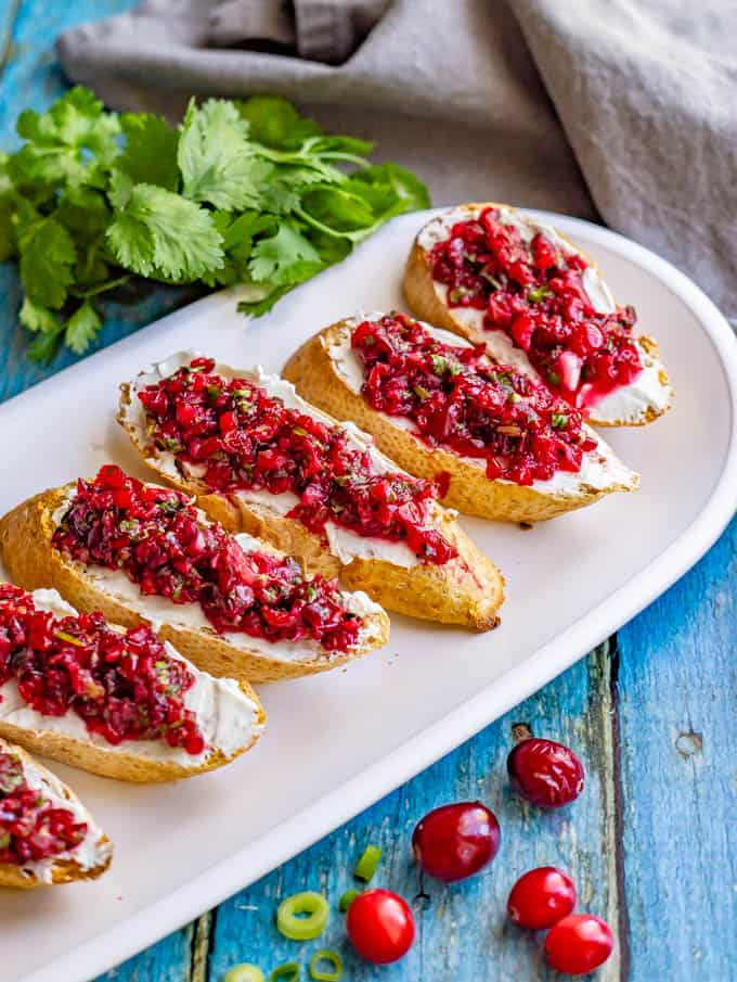 Baguette slices with cream cheese and fresh cranberry salsa on a white platter