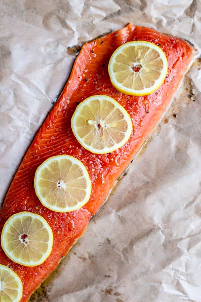 Raw wild-caught salmon on a pice of parchment paper with lemon slices on top